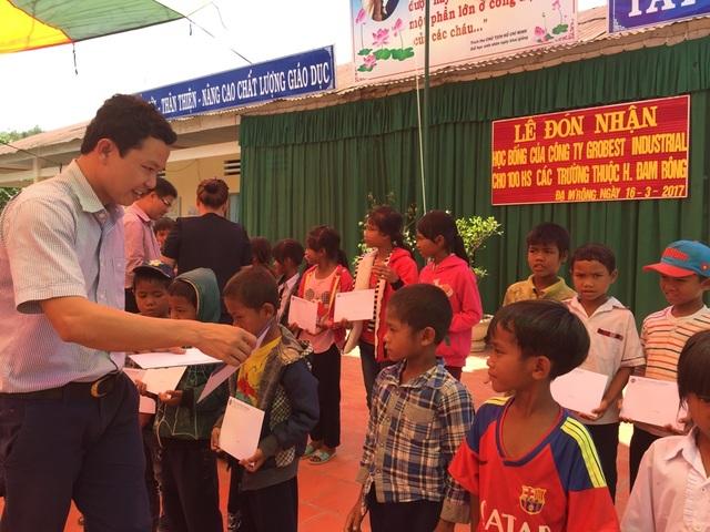 Ông Nguyễn Quang Mạnh, Trưởng đại diện Công ty Grobest Việt Nam, khu vực Ninh Thuận - Bình Thuận trạo học bổng cho các em học sinh trường tiểu học xã Đạ M'Rông (Đam Rông)