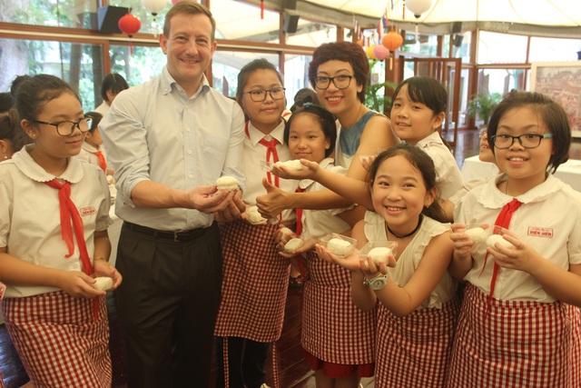 Đại sứ Bertrand Lortholary cầm chiếc bánh trung thu do chính tay ông làm cùng với các em nhỏ.