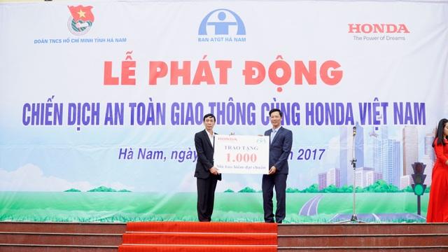Ông Vũ Quang Tâm - Phó Tổng GĐ Công ty HVN trao tặng biển tượng trưng 1.000 mũ bảo hiểm cho Ban ATGT tỉnh Hà Nam