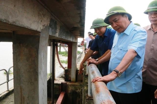 Thủ tướng Nguyễn Xuân Phúc thị sát đập tràn Lạc Khoái, xã Gia Lạc, huyện Gia Viễn (Ninh Bình) nghe lãnh đạo tỉnh Ninh Bình báo cáo mực nước lũ tại đây những ngày qua.