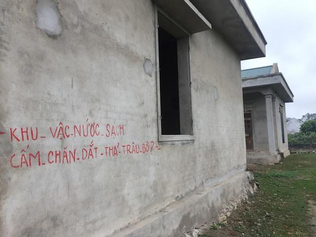 Trên tường công trình này vẫn còn dở dang chưa được quét vôi hoặc lăn sơn, mà nhường lại cho nét chữ dơ bẩn viết lên.