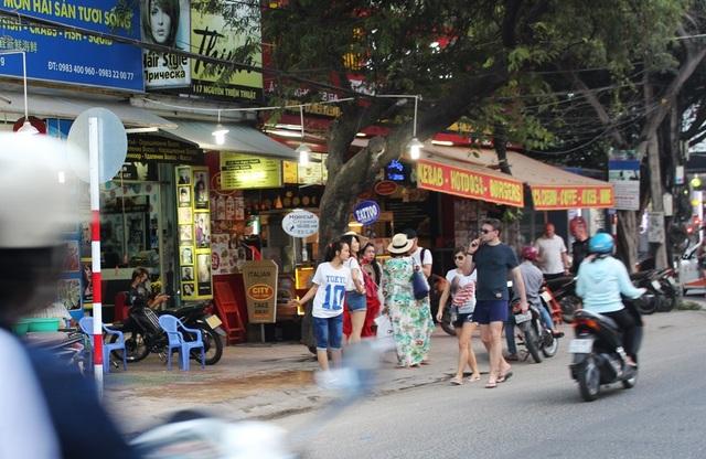 Hàng loạt quán giải khát trên đường Nguyễn Thiện Thuật đưa bàn ghế ra chiếm vỉa hè khiến du khách phải đi lộn xộn trên lòng đường