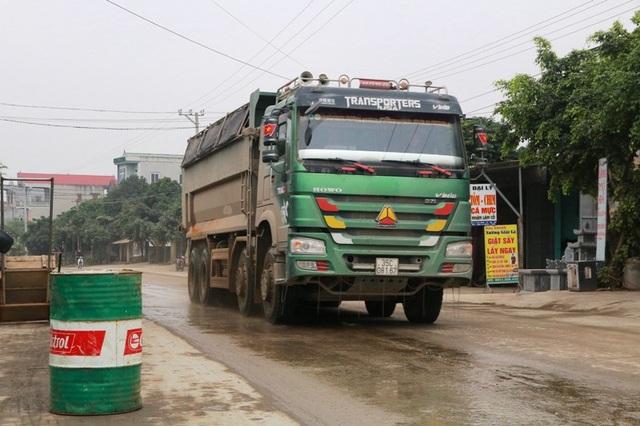 Người dân phải dùng thùng phuy ngăn không cho những chiếc xe siêu tải chạy sát vào nhà mình.