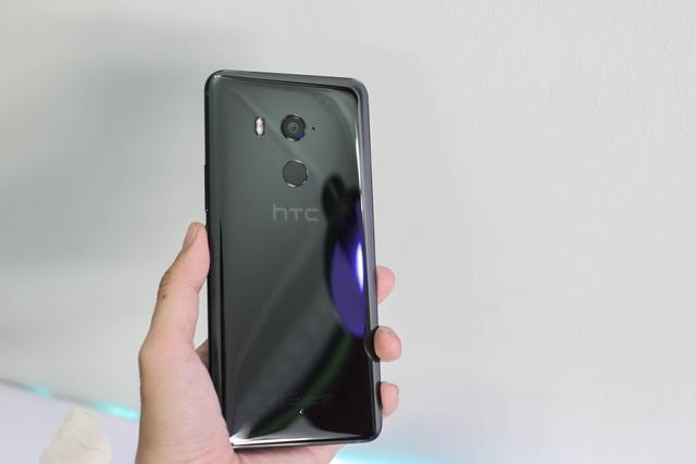 """Ở mặt sau của máy, HTC thiết kế U11 Plus vẫn tương tự thế hệ trước với bề mặt chất lỏng nhưng làm cho mặt lưng """"trong suốt"""" đúng nghĩa, có thể thay đổi màu sắc tùy theo nguồn ánh sáng hướng vào máy."""