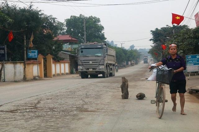 Người dân dùng khúc gỗ, gạch đá ngăn xe tải chạy vào sát nhà bên đường tránh gây mất an toàn.