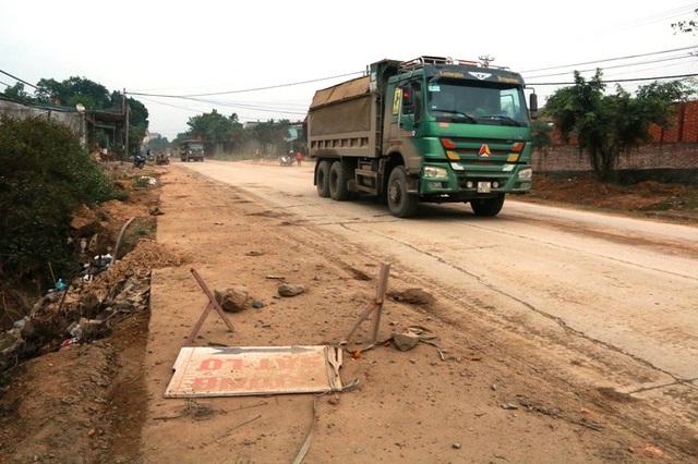 Biển cảnh báo sạt lở đất bị xe tải chạy qua làm đổ, gây mất nguy hiểm cho người đi đường.