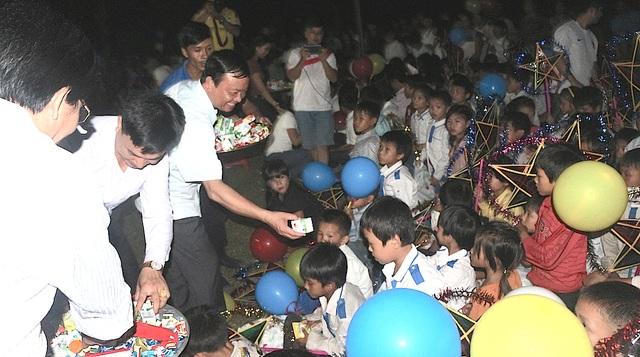 Thành viên CLB liên quân báo chí và Chủ tịch UBND huyện Tương Dương phát quà cho các em.