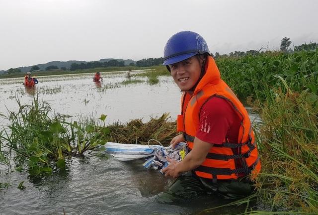 Ngâm mình trong nước lũ gặt lúa giúp dân