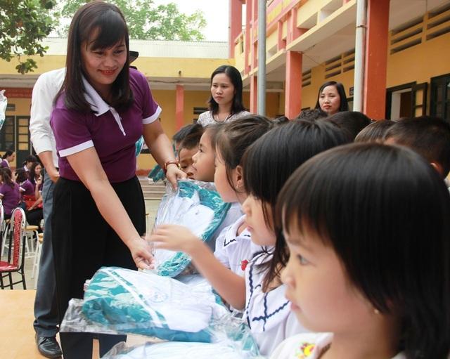 Cô giáo Vũ Thị Thúy Hà, Hiệu trưởng trường tiểu học Đông Vệ 2 trao áo ấm đến học sinh vùng lũ