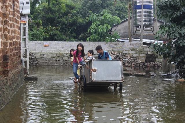 Đám trẻ vẫn vô tư chơi cùng nước lụt.