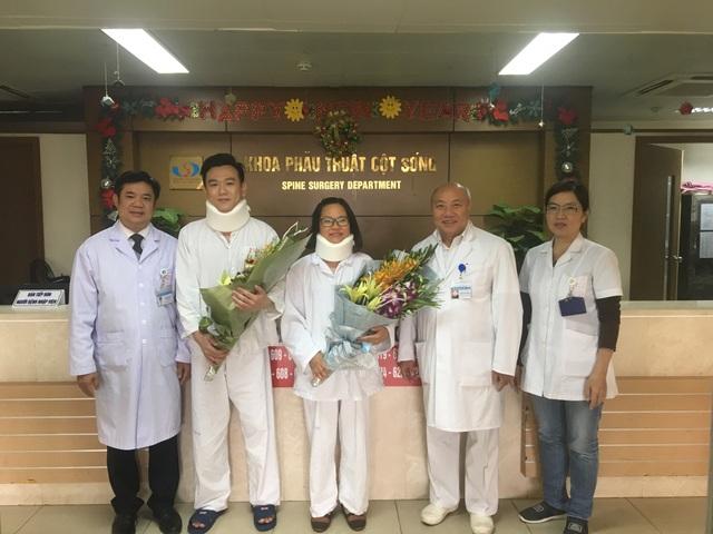 PGS-TS Nguyễn Văn Thạch, nguyên Phó Giám đốc BV Việt Đức (phải) và TS.BS Đinh Ngọc Sơn, Trưởng khoa Phẫu thuật cột sống BV Việt Đức tặng hoa cho 2 bệnh nhân trước khi xuất viện