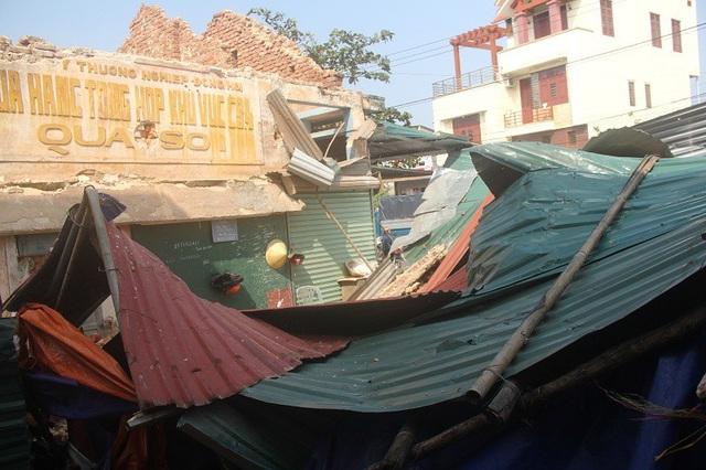 Mảng tường bị sập đè lên các mái tôn ngay trên đầu nhiều tiểu thương và làm sập một khu vực mái che trong chợ
