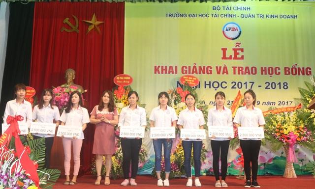 Bà Hoàng Thị Bài (giữa), đại diện Quỹ Khuyến học Việt Nam trao học bổng giải Golf Vì sinh viên vượt khó học giỏi do báo Đầu tư tổ chức đến sinh viên Trường ĐH Tài chính - Quản trị Kinh doanh