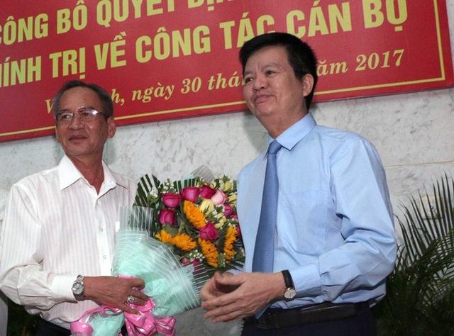 Ông Lữ Văn Hùng (trái) nhận hoa chúc mừng từ ông Mai Văn Chính