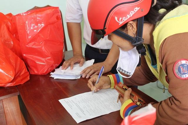 Người dân vùng bão ở TP Nha Trang ký nhận sau khi nhận quà cứu trợ bão số 12 từ nước Nga