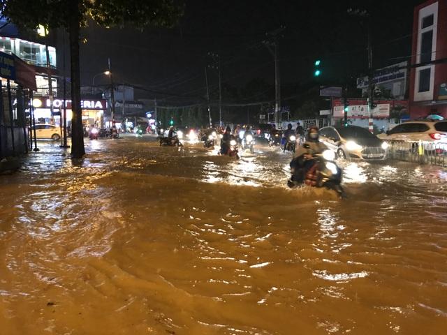 Nước ngập sâu lút nửa bánh xe máy khiến người tham gia giao thông vô cùng khốn đốn.
