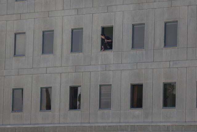 Một cảnh sát nhìn ra từ cửa sổ tòa nhà quốc hội Iran (Ảnh: Reuters)