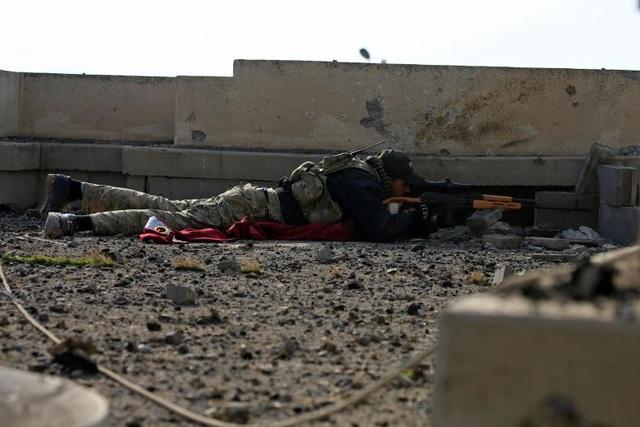 Một lính bắn tỉa thuộc quân đội chính phủ Iraq chọn vị trí tác chiến tại một bệnh viện bị tàn phá trong cuộc giao tranh với nhóm khủng bố IS ở quận Wadha, phía đông Mosul.