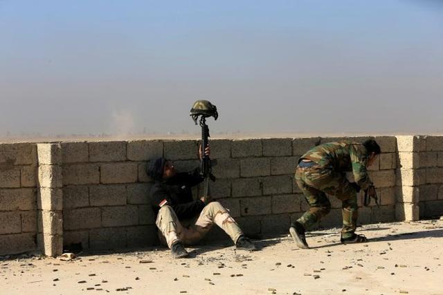 Một lính Iraq sử dụng chính mũ bảo hiểm của mình cắm trên họng súng để tạo mục tiêu giả, đánh lạc hướng một tay súng bắn tỉa của IS ở phía nam Mosul.