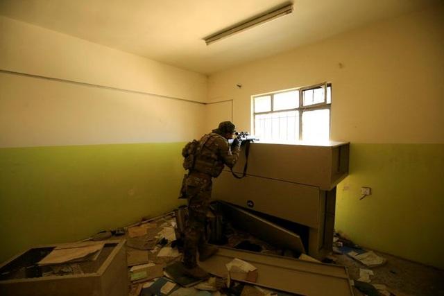 Do đặc thù chiến đấu nên vị trí hoạt động của các tay súng bắn tỉa thường nằm trong các góc tối hoặc các căn hầm và chĩa họng súng về phía mục tiêu ở bên ngoài. Trong ảnh: Một tay súng bắn tỉa thuộc lực lượng phản ứng nhanh Iraq ngắm bắn từ cửa sổ của một căn nhà hoang tàn trong một cuộc giao tranh với IS ở Mosul.
