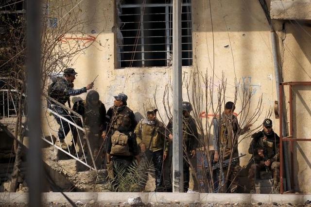 Lực lượng đặc nhiệm Iraq và các cảnh sát liên bang nấp sau một bức tường để tránh tầm mắt của các tay súng bắn tỉa trong cuộc quyết đấu với IS ở phía tây Mosul.