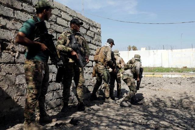Các thành viên thuộc lực lượng phản ứng nhanh Iraq chuẩn bị băng qua đường để tránh bị trúng đạn của các tay súng bắn tỉa IS ở phía tây Mosul.