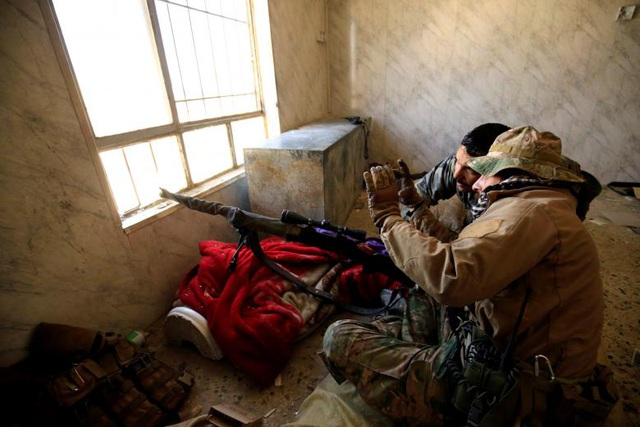 Hai binh sĩ Iraq được giao nhiệm vụ bắn tỉa trao đổi với nhau bên trong một căn nhà ở Mosul.