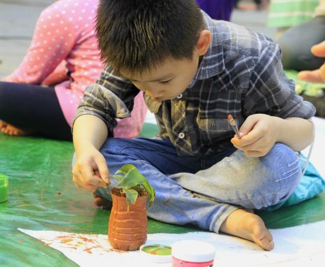 Em nhỏ say sưa trải nghiệm đồ tái chế trồng cây