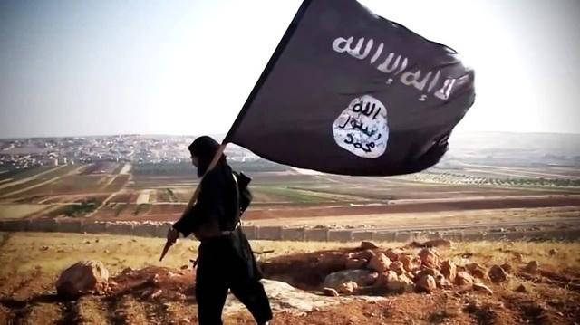 Một tay súng mang cờ IS (Ảnh: PBS)