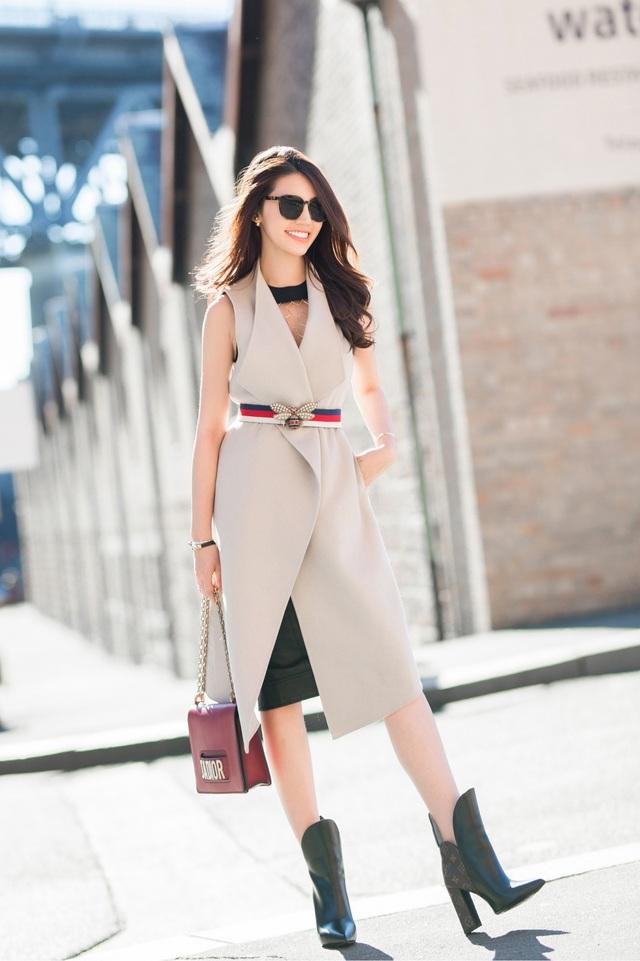 Hoa hậu Thế giới người Việt tại Úc 2015 biến hoá theo phong cách thanh lịch với chiếc áo phom dài màu trắng kem kết hợp chân váy ngang gối bên trong, thắt lưng 3 màu. Ngoài đôi boots có thiết kế lạ mắt, túi xách màu đỏ rượu đi kèm cũng là điểm nhấn đáng chú ý.