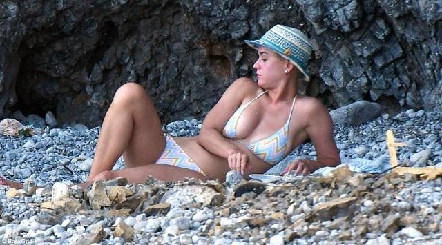 Ngôi sao ca nhạc thư giãn nằm tắm nắng và đọc sách trên biển.