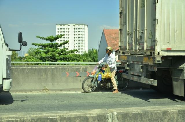 Một người dân chạy vào làn đường xe ô tô trên cầu Phú Mỹ để bán bánh mì cho tài xế