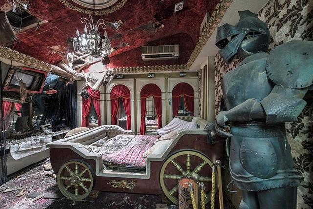 Một căn phòng thiết kế theo lối trung cổ với giường ngủ là cỗ xe và bộ áo giáp