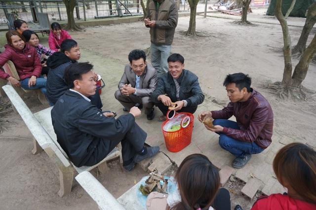 Du khách nghỉ ngơi ăn tạm đồ trước khuôn viên đền Thiên Trường.