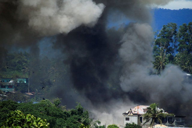 Tổng thống Philippines Rodrigo Duterte đã áp đặt thiết quân luật trên toàn đảo Mindanao từ ngày 23/5, ngay sau khi các cuộc giao tranh nổ ra. Trong ảnh: Khói đen bốc lên nghi ngứt từ một ngôi nhà bị phóng hỏa tại Marawi.
