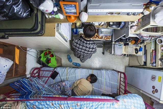 """Một giải pháp thay thế khác ở Hong Kong là những căn hộ """"quan tài"""". Người phụ nữ này sống cùng con trai với giá thuê nhà khoảng 400 bảng Anh/tháng."""
