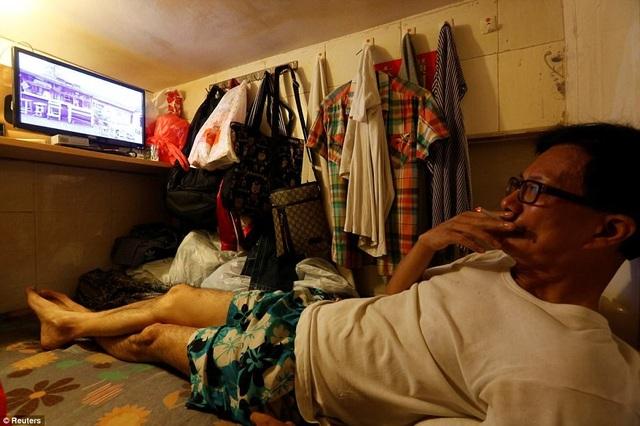 """Simon Wong, 61 tuổi, sống một mình trong căn phòng """"quan tài"""" với giá thuê 183 bảng Anh/ tháng. Nơi này chật hẹp đến mức không thể đứng thẳng, chỉ đủ duỗi khi ngủ và treo một số món đồ cần thiết."""