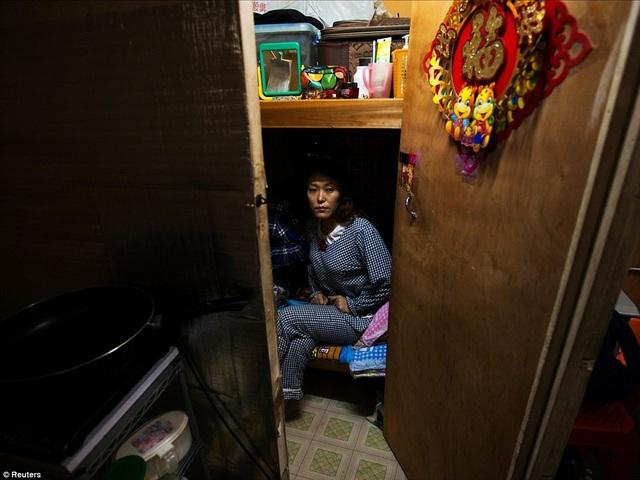 Ở một nơi khác tại Hong Kong, Li Rong, 37 tuổi, dùng chiếc giường dưới trong căn hộ của mình để ngủ, còn giường trên là nơi cất giữ đồ dùng.