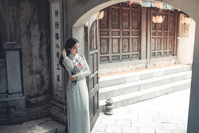 Bộ trang phục màu trắng nền nã với họa tiết hoa sen làm tôn vẻ duyên dáng, yêu kiều của cô gái trẻ.
