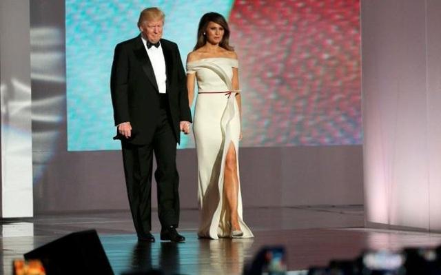 Tân Tổng thống Donald Trump trong bộ vest đen truyền thống thắt nơ sánh bước cùng Đệ nhất phu nhân Melania trong váy dạ hội trắng tinh tế khi bước ra khán phòng khiêu vũ. (Ảnh: Reuters)