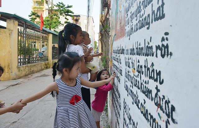 Trẻ em trong xóm vẫn thường hay vui chơi bên cạnh những bức tranh mà cụ Thịnh phóng tác.