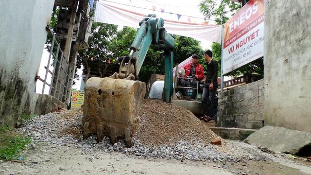 Người dân huy động máy xúc để di chuyển đống đá, sỏi chặn lối đi trước khi Chủ tịch TP Hà Nội Nguyễn Đức Chung về xã.