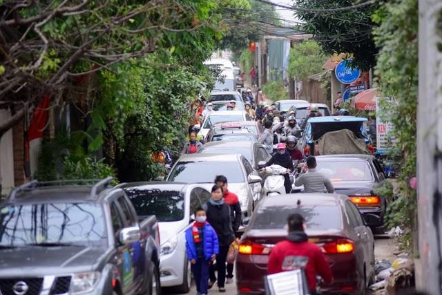 Hàng đoàn xe ô tô và xe máy nối đuôi nhau thành hàng dài, nhiều vị khách sốt ruột chấp nhận xuống xe đi bộ vào vườn hoa.