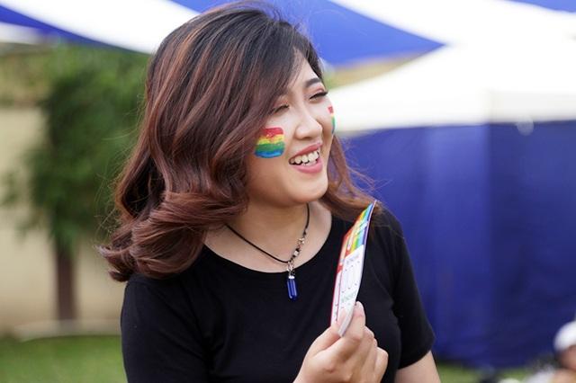 Một cô gái xinh đẹp vẽ lá cờ 6 màu lên mặt, thể hiện tinh thần ủng hộ cộng đồng LGBT
