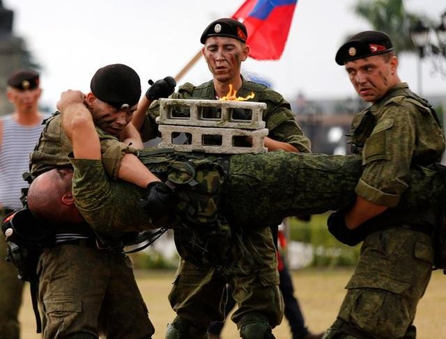 Guardian đưa tin ngày 5/1, các binh sĩ Nga đã trình diễn các kỹ thuật chiến đấu tại công viên quốc gia Luneta ở thủ đô Manila, Philippines. Đây là một hoạt động trong chuyến thăm hữu nghị kéo dài 5 ngày của các lực lượng quân đội Nga tại Philippines. Trong ảnh: Màn trình diễn đập vỡ khối gạch trên bụng nhằm tăng cường sức chịu đựng của các binh sĩ Nga. (Ảnh: EPA)