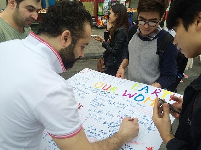 Du khách nước ngoài hào hứng viết lời chúc dành cho những người phụ nữ mà họ thương yêu.