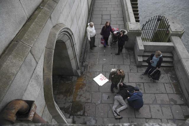 Trong số 5 nạn nhân thiệt mạng có 3 người là người đi bộ trên cầu Westminster - một địa danh nổi tiếng ở thủ đô London và cũng là nơi thu hút lượng lớn khách du lịch tới Anh. Trong ảnh: Một người bị thương nằm trên cầu Westminster trước khi lực lượng cứu hộ tới trợ giúp (Ảnh: Reuters)