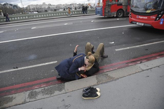 Một phụ nữ nhanh chóng cứu giúp một nạn nhân trong vụ tấn công. (Ảnh: Reuters)