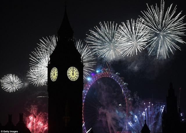 Đồng hồ Big Ben điểm 12 giờ đêm trong thời khắc chuyển giao giữa năm cũ và năm mới khi pháo hoa rực sáng bầu trời thủ đô London, Anh (Ảnh: Getty)
