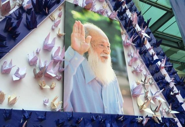 Hình ảnh của thầy Văn Như Cương được treo trang trọng trong khung hình logo của nhà trường, bao quanh là những con hạc giấy. Triển lãm đồng thời diễn ra tại hai cơ sở vào cùng ngày 18/11.